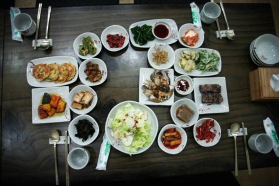 Typical Korean-style table setting: tons of small side-dishes surround the main dish, which hadn't arrived at this point.