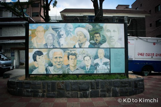 A faded mural of famous Asian icons in the park
