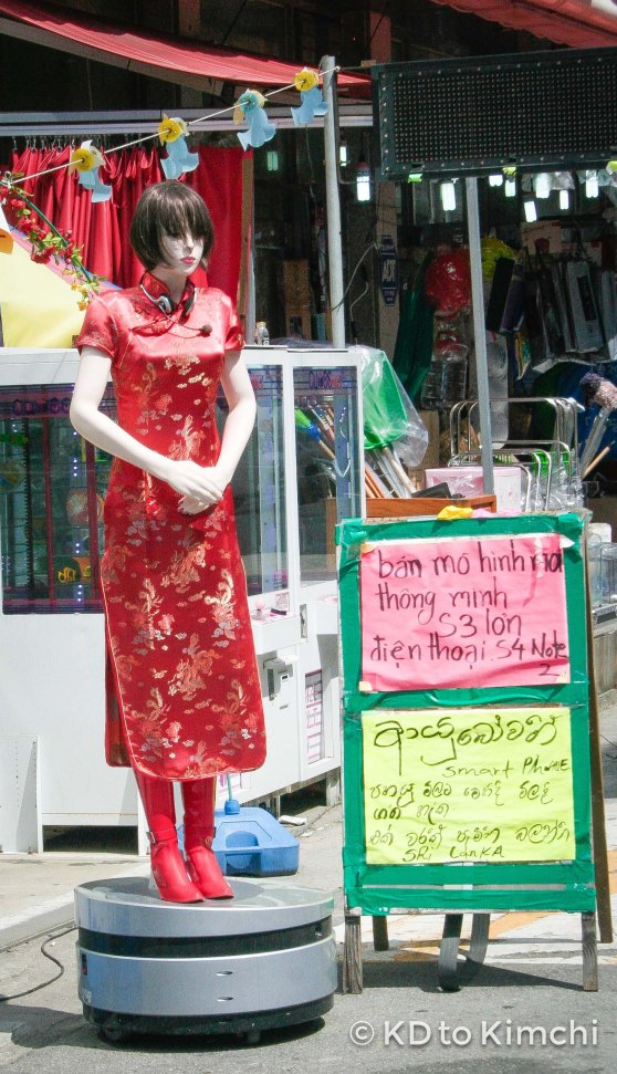 A Chinese-inspired model outside a cellphone shop