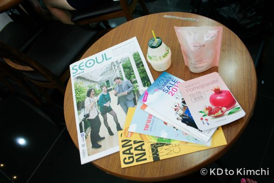 "My swag: coupon book for the 2013 Seoul Summer Sale, a copy of SEOUL Magazine with Mimsie Ladner of ""Seoul Searching"" blog on the cover, free cosmetics, and a free banana milk"